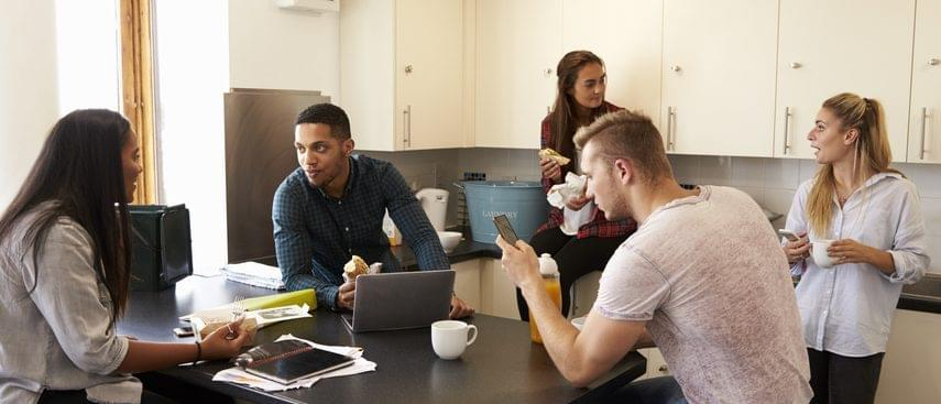 Group of students talking in a kitchen